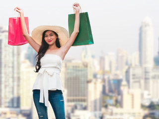Happy young woman with shopping bags enjoying in shopping, Asian girl is having fun with her purchases in city. Consumerism and lifestyle concept