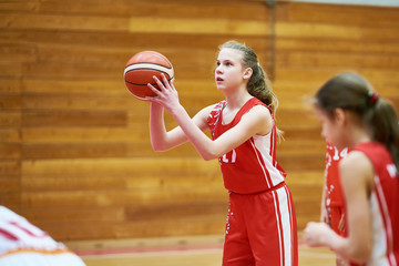 Girl basketball player throws ball in game
