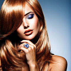 Face of a beautiful woman with sapphire jewelry ring on finger