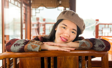 Portrait of fashionable asian girl in a wooden tourist boat.