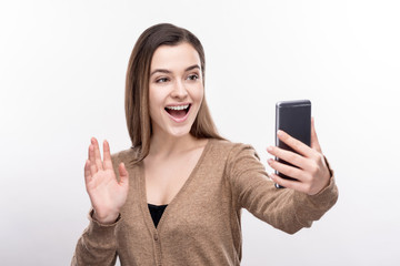 Perfect shot. Charming young woman posing for the camera, waving at it while taking selfies, standing isolated on a white background