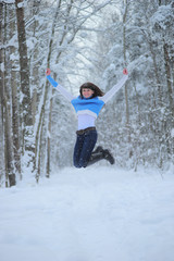 happy brunette jumping in the park in the snow