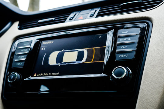 Car dashboard display showing next maneuver on the screen using the car parking sensors