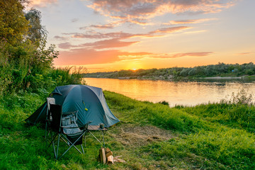 Foto auf AluDibond Camping Camping by the river. Tents and camping equipment.