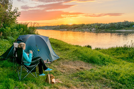 Young woman in camping with a tourist tent on the river bank. Russia.