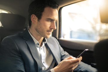 Man texting on his smart phone while traveling by car