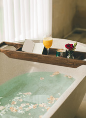Bright Bathroom at Home. Bath with Flower Petals and Salt. Tray over the Bath with Orange Juice, Notepad and Candles.