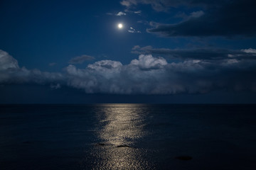 Night sky with full moon and reflection in sea, beautiful clouds.
