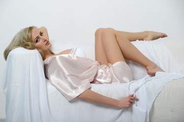 blonde in a silk dressing gown on the sofa