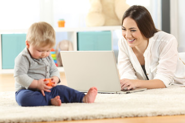 Mother working with a laptop and baby playing