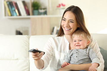 Happy mother and baby watching tv at home