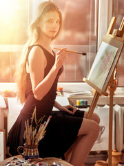 Artist painting on easel in studio. Girl paints with brush in morning sunlight dawn light toning. Indoor home interior for handmade crafts with window background. Drawing of spring flowers.