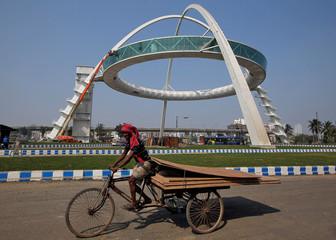 A man transports plywood sheets in a rickshaw next to Kolkata Gate on the outskirts of Kolkata