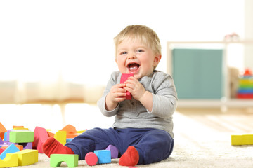 Baby laughing and playing with toys on a carpet