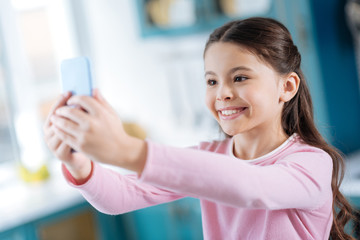 Joy. Pretty alert dark-eyed dark-haired schoolgirl smiling and taking selfies while holding her phone in front of her