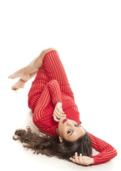 young beautiful woman in a red transparent dress lying on a white floor