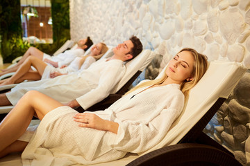People in bathrobes are resting in the spa salon. Friends relax on weekends.
