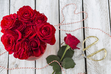 on a white wooden table red roses, ribbon and scissors