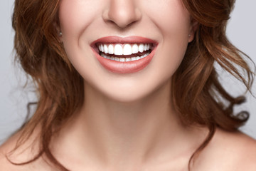 Healthy white smile close up. Beauty woman with perfect smile, lips and teeth. Beautiful Model Girl with white teeth and perfect skin. Teeth whitening.