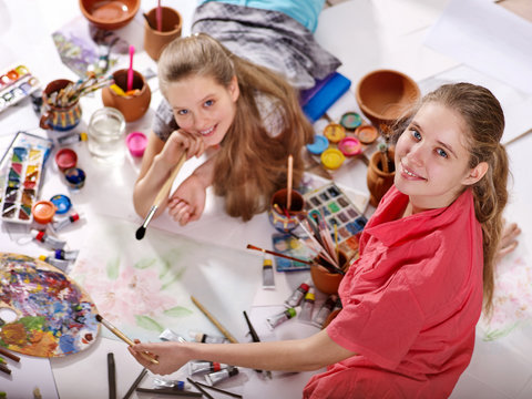 Authentic artist children girl paints with set palette watercolor paints palette and brush in morning sunlight . Painting in studio on floor.Top view indoor home interior handmade crafts .