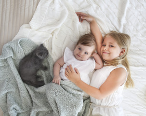 Portrait of two small pretty girls with kitten