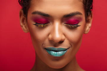 Macro image of charming african american woman being fashionable and trendy wearing colorful cosmetics posing with closed eyes, over red wall