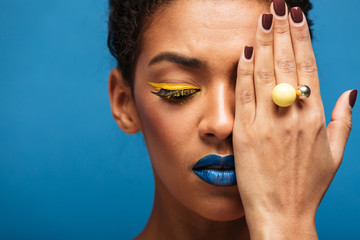 Closeup beauty photo of relaxed mixed-race woman with fancy makeup posing on camera covering one eye with hand, isolated over blue background