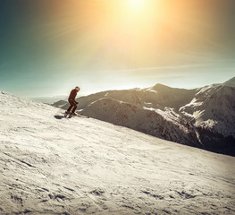 Nice mountains view at sunny day with skiers under blue sky with