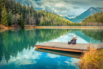 Happy young woman sitting on the wooden pier and drink coffee, m