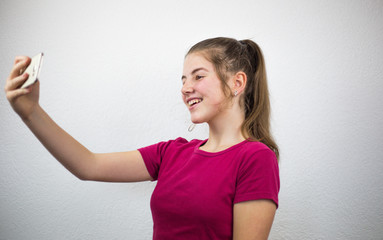 Young beautiful teenage blonde girl taking photo of herself while smiling on her mobile smart phone wearing pink purple T-shirt on a white background