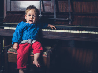 Cute little baby boy sitting by piano