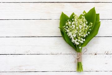 a bouquet of flowers fragrant lilies of the valley on white wooden background with copy space. mock up for text, for phrases, for lettering