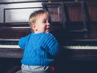 Cute little baby boy sitting by piano