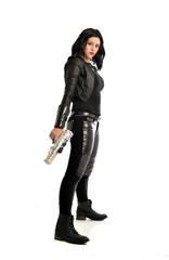 full length portrait of black haired girl wearing leather outfit. standing pose while holding a gun, isolated on a white studio background.