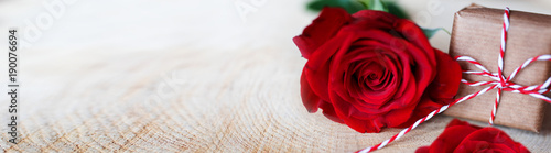 Red roses with a gift on bright rustic wood