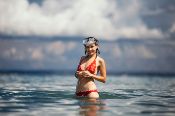A young woman is standing in the sea against a background of clouds. She is dressed in a red swimsuit and on her head a mask for diving.