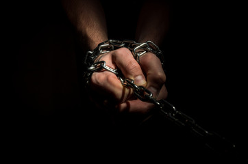 Hands are chained in chains isolated on black background