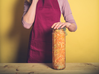 Young woman with massive jar of kimchi