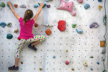 girl climbing on an artificial rock wall