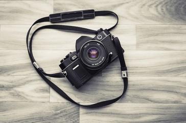 un ancien appareil photo avec un flash installé au milieu d'un fond en bois marron