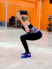 Young model girl makes exercises at the gym in front of mirror