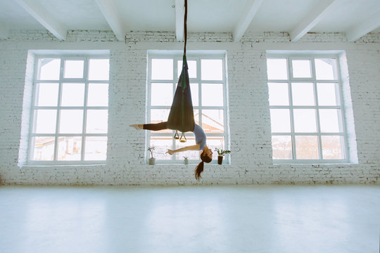 Young woman doing fly yoga exercise and stretching in front of windows on white background in loft interior studio.