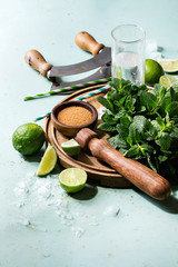 Ingredients for making mojito cocktail. Bundle of fresh mint, whole and sliced limes, brown sugar, crashed ice cubes, glass of soda water, cocktail tubes on wooden board over green pin up background.
