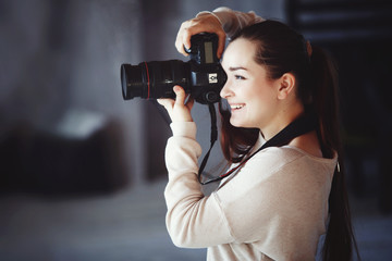 Сute girl takes pictures with a professional camera