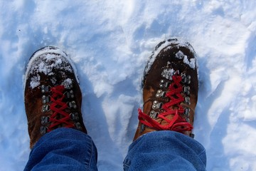 A pair of hiking boots in the snow on a close up view.