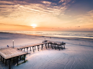 Sunrise over the beach and wooden dock aerial view
