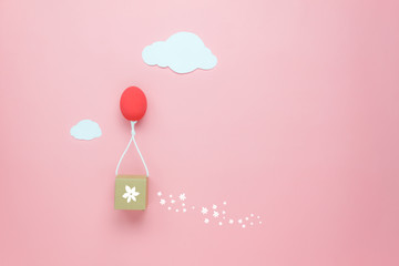 Top view shot of arrangement decoration Happy Easter holiday background concept.Flat lay colorful Easter egg balloon fly transfer blossom gift box on sky pink paper with cloud.Design pastel tone.