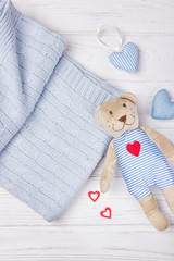 Cute teddy bear, baby stuff and hearts on a light background. Top view, free space