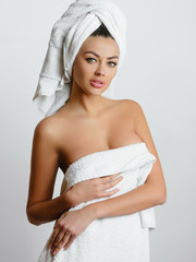 Beautiful young woman in towel all ready to get spa treatment. girl is sexually posing