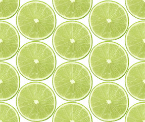 Seamless background with slices of lime fruits on white